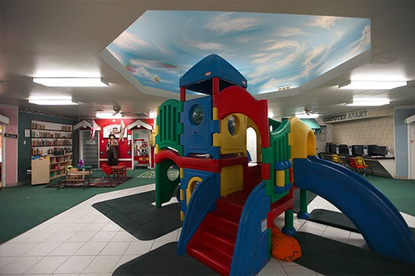 Colorful plastic playhouse with slides indoor at a Preschool & Daycare Serving Hesperia, CA