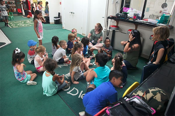 Teachers with group of multi ethnic young little kids gather around at a Preschool & Daycare Serving Hesperia, CA