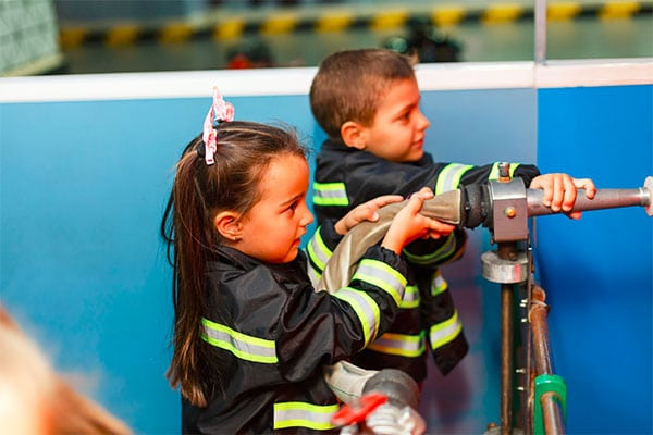 Preschool boy and girl wearing firefighter attire with firefighting hose on a demo at a Preschool & Daycare Serving Hesperia, CA