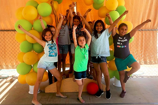 Group of happy teen girls posing and raising two hands in a green and yellow balloon background at a Preschool & Daycare Serving Hesperia, CA