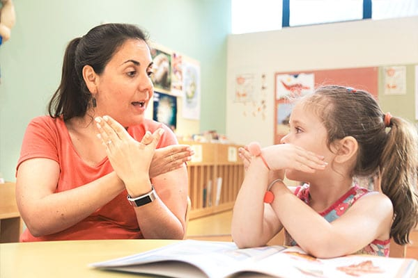 Teacher and a young little girl teaching a girl with bird hand gestures at a Preschool & Daycare Serving Hesperia, CA