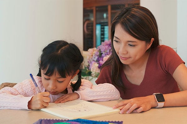 Beautiful teacher watching a young little preschool girl drawing on a paper at a Preschool & Daycare Serving Hesperia, CA
