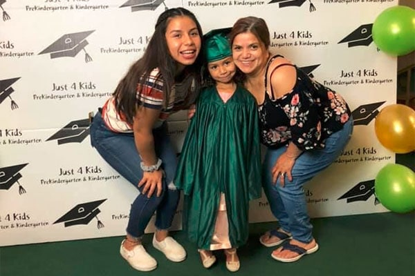 Happy teacher with mother and daughter wearing graduation toga at a Preschool & Daycare Serving Hesperia, CA