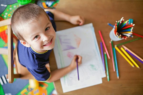 Happy young little kid boy while coloring and drawing on a paper with color pencils on the table at a Preschool & Daycare Serving Hesperia, CA