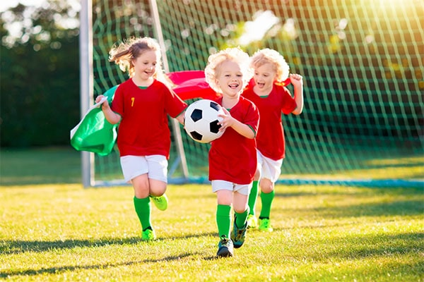 Happy preschoolers wearing red soccer shirt running holding two holding a flag and one with soccer ball at a Preschool & Daycare Serving Hesperia, CA