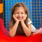 Happy cute little girl with two hands holding her face in a slide at a Preschool & Daycare Serving Hesperia, CA