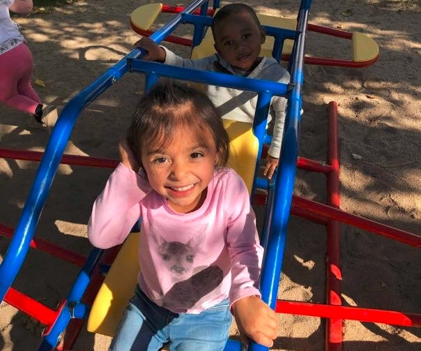 Happy cute little preschool girl wearing pink sweatshirt playing on monkey bars at the playground at a Preschool & Daycare Serving Hesperia, CA