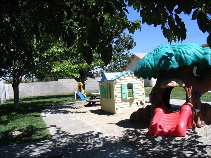 plastic playhouse and plastic slide in the school yard at a Preschool & Daycare Serving Hesperia, CA