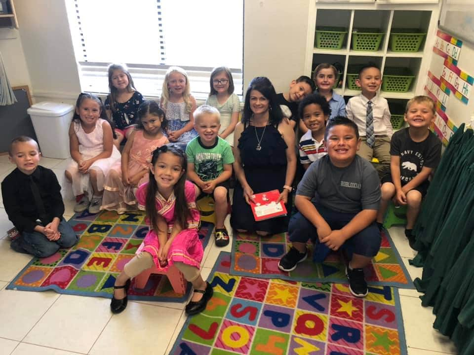 Group of children smiling with their teacher at a Preschool & Daycare Serving Hesperia, CA