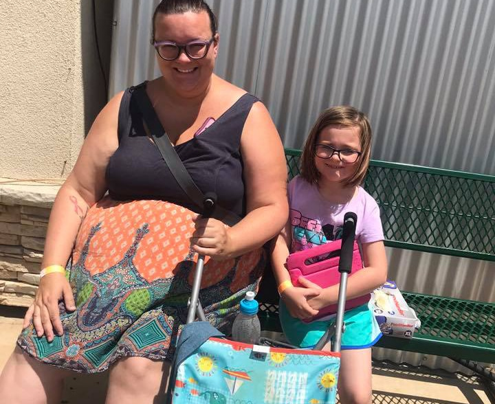 Happy mom and daughter both wearing glasses with a baby stroller at the school yard at a Preschool & Daycare Serving Hesperia, CA