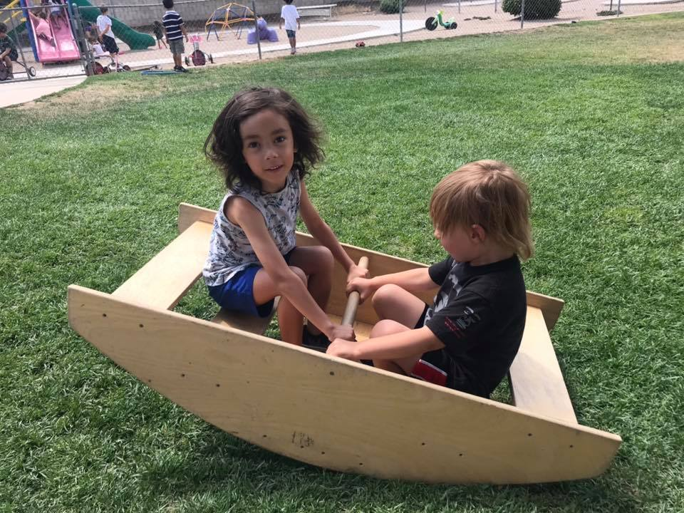 Two little preschool kids on a wooden DIY seesaw on the playground at a Preschool & Daycare Serving Hesperia, CA at a Preschool & Daycare Serving Hesperia, CA
