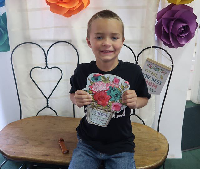 A kid boy holding a colorful flower designed artwork for mom at a Preschool & Daycare Serving Hesperia, CA