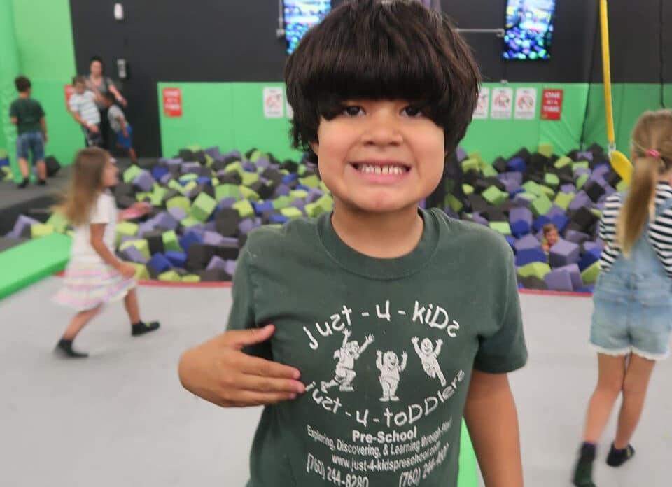 Smiling preschool kid wearing just-4-kids school shirt at an indoor play center at a Preschool & Daycare Serving Hesperia, CA