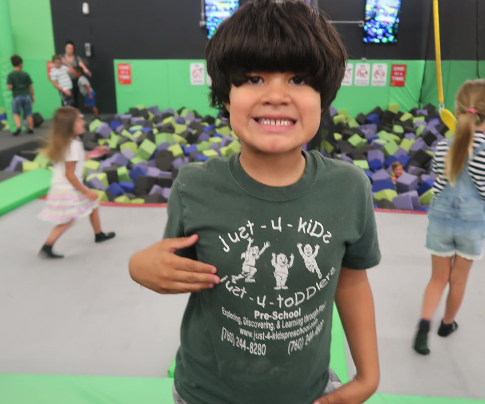 Smiling preschool kid wearing just-4-kids school shirt at an indoor play center at a Preschool & Daycare Serving Hesperia, CA