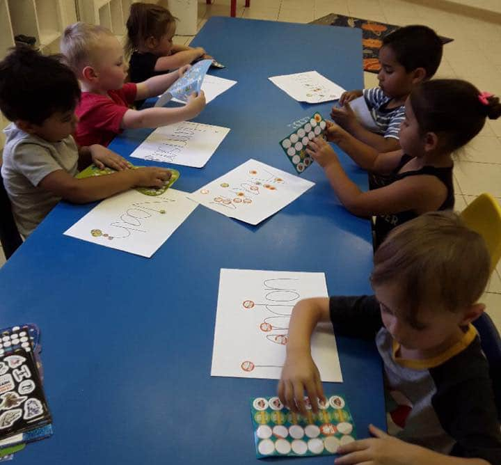 Group of preschool kids in the table working with stickers and putting them on paper and drawing at a Preschool & Daycare Serving Hesperia, CA