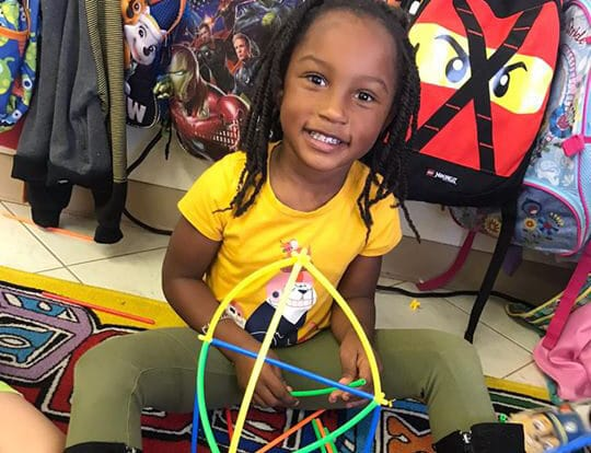 happy african american girl playing colorful stick building blocks at a Preschool & Daycare Serving Hesperia, CA