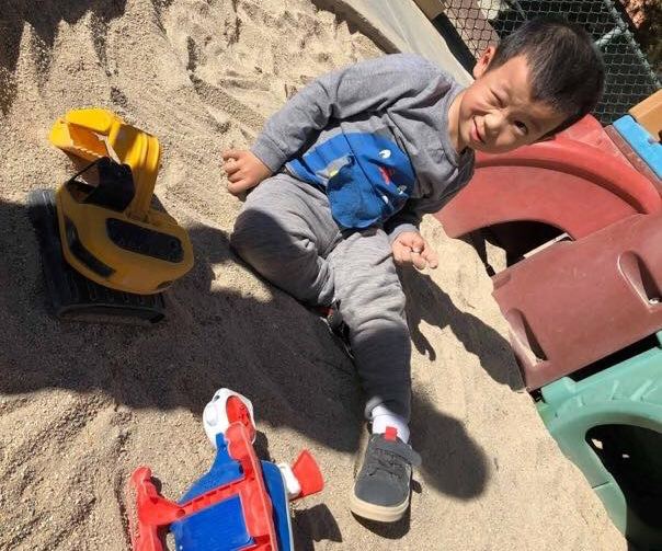 Winking preschool kid boy playing on the sand at a playground at a Preschool & Daycare Serving Hesperia, CA