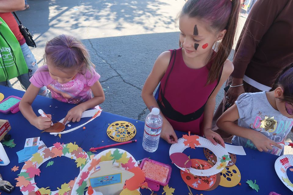 Preschoolers doing an art project cutting colorful flower shaped design on a cut paper plates at a Preschool & Daycare Serving Hesperia, CA