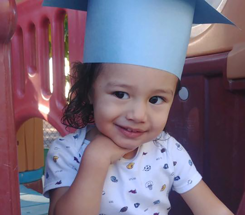 Cute preschool little girl smiling wearing a blue paper graduation hat while in the playground at a Preschool & Daycare Serving Hesperia, CA