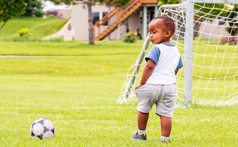 African american preschool boy looking at the soccer ball while in the field next to the soccer goal at a Preschool & Daycare Serving Hesperia, CA