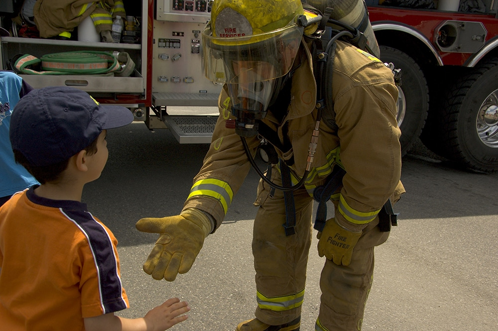 Firefighter in uniform greeting a child at a Preschool & Daycare Serving Hesperia, CA