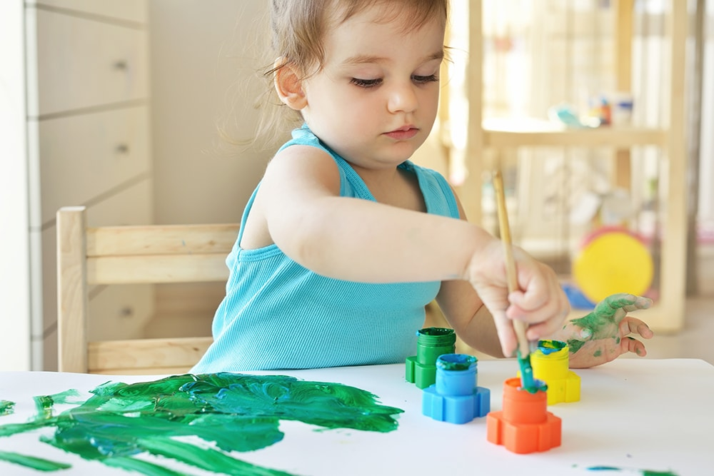 Cute little toddler child painting with paintbrush and colorful paints. Adorable baby girl drawing on white paper near window in light room at a Preschool & Daycare Serving Hesperia, CA
