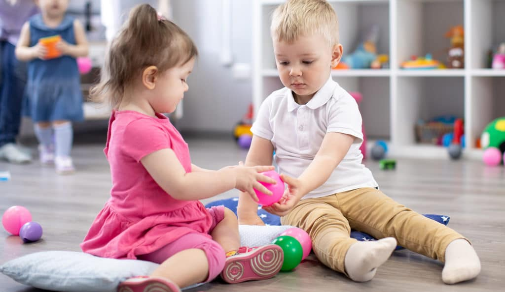 Little toddlers boy and a girl play together in nursery room. Preschool children at a Preschool & Daycare Serving Hesperia, CA