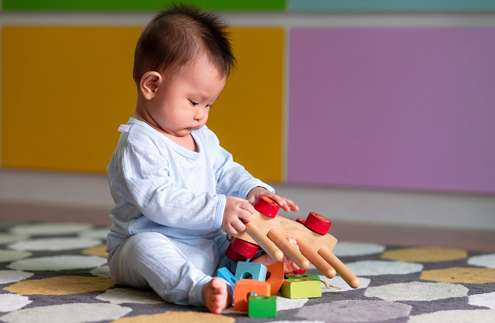 Asian male toddler playing with his toy on the floor. Curious look. at a Preschool & Daycare Serving Hesperia, CA