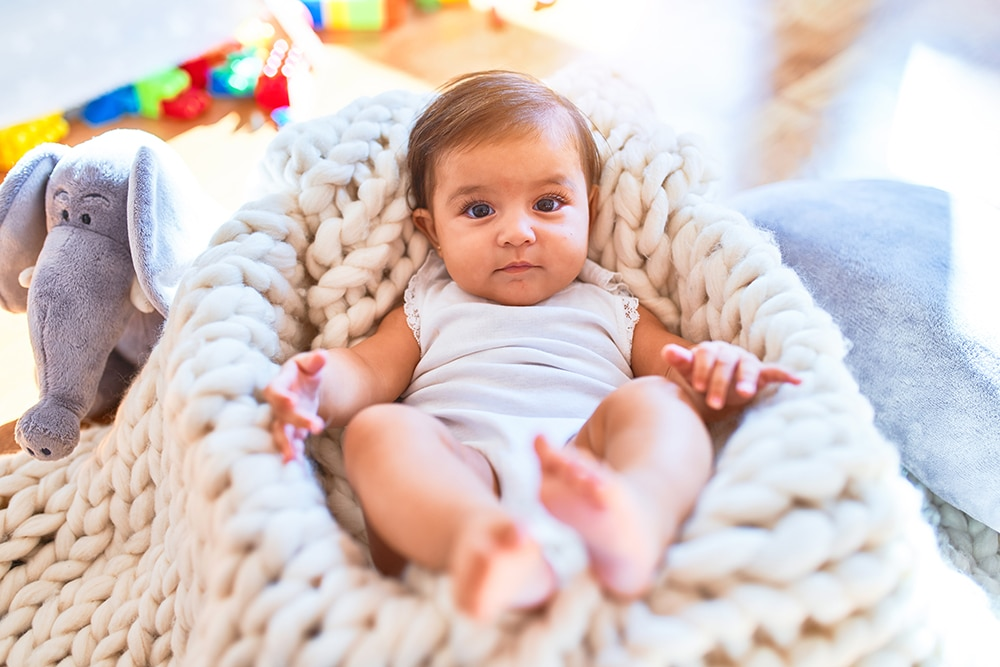 Beautiful infant happy at kindergarten around colorful toys lying inside crib at a Preschool & Daycare Serving Hesperia, CA