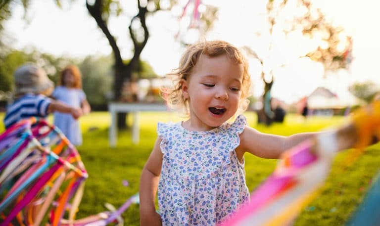A front view of small toddler girl on birthday party outdoors in garden in summer at a Preschool & Daycare Serving Hesperia, CA