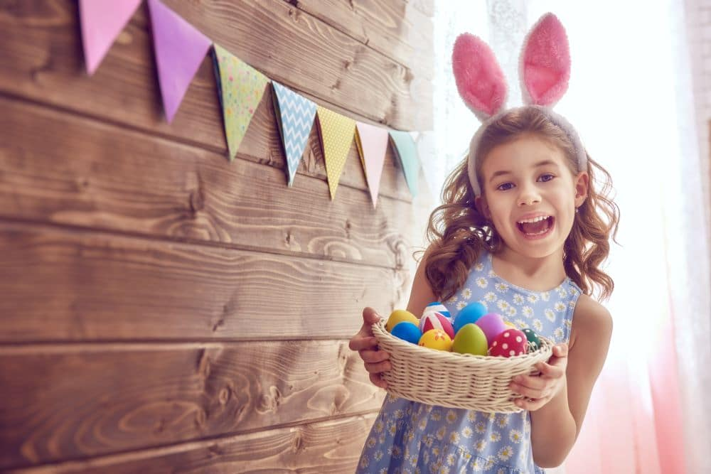 Cute young little girl wearing rabbit ears holding a basket full of colorful painted eggs at a Preschool & Daycare Serving Hesperia, CA