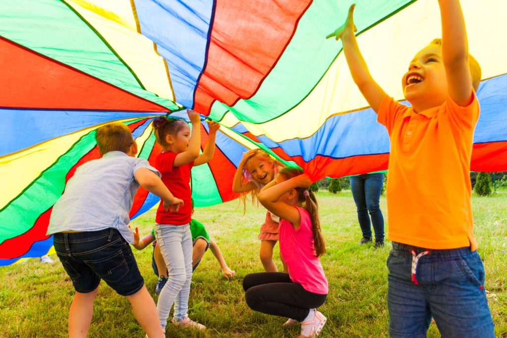 Group of preschoolers enjoying playing under a colorful tent cover at a Preschool & Daycare Serving Hesperia, CA