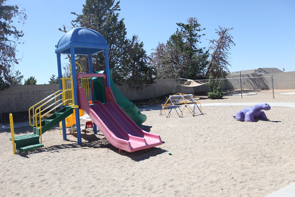 sandy playground with a colorful slide and a geo-dome climber jungle gym, violet dino-ride at a Preschool & Daycare Serving Hesperia, CA