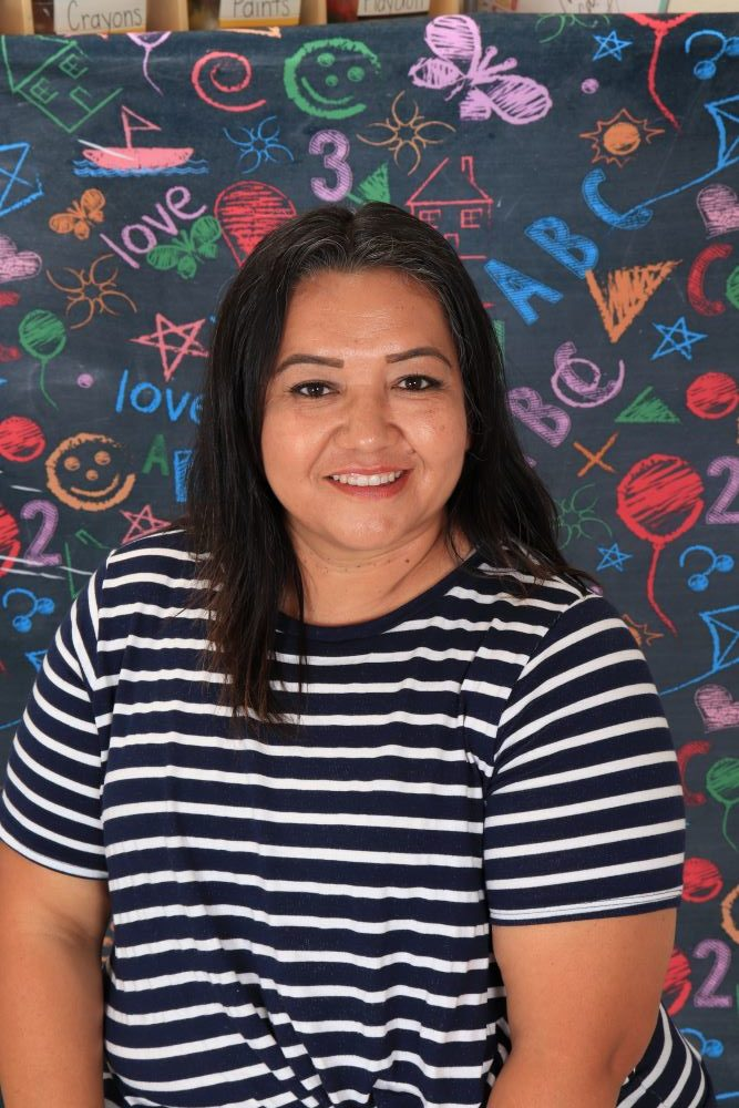 Ms_Ana happy preschool teacher on a colorful chalk design wall background at a Preschool & Daycare Serving Hesperia, CA