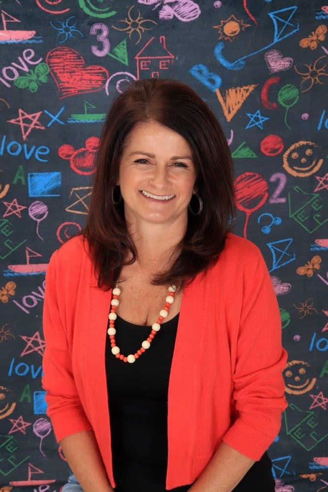 Ms_Jennie happy preschool teacher on a colorful chalk design wall background at a Preschool & Daycare Serving Hesperia, CA