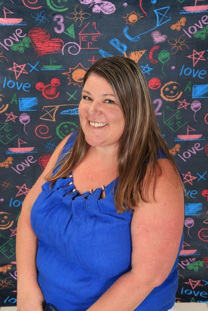Ms_Kristin happy preschool teacher on a colorful chalk design wall background at a Preschool & Daycare Serving Hesperia, CA