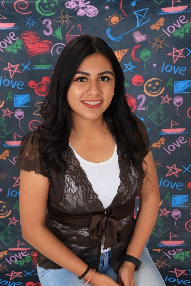Ms_Verenise happy preschool teacher with a colorful chalk design wall background at a Preschool & Daycare Serving Hesperia, CA
